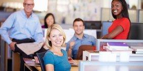Fröhliche Menschen in einem Großraumbüro