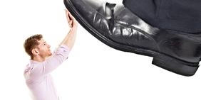 Mann hält Schuh, der nach ihm Tritt fern
