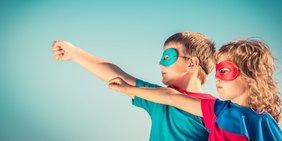 Zwei Kinder mit Superheld-Kostümen